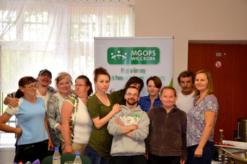 Zdjęcie grupowe ludzi przed reklamą Miejsko Gminnego Ośrodka Pomocy Społecznej w Więcborku