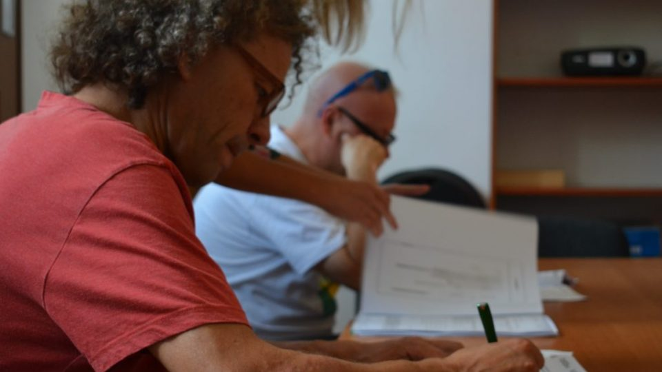 Zdjęcie trzech osób podpisujących dokumenty