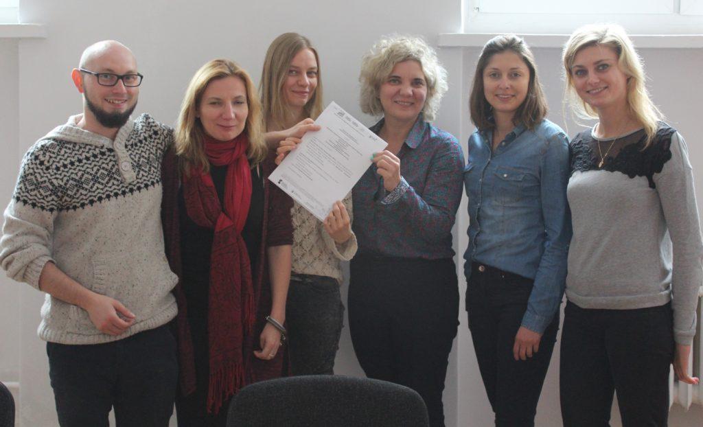 Zdjęcie pięciu kobiet i mężczyzny z dokumentem