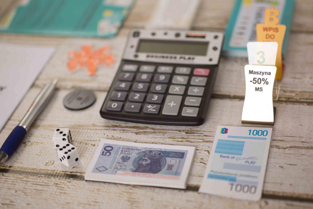 Zdjęcie elementów gry Business Play - kalkulator, banknoty i kości do gry