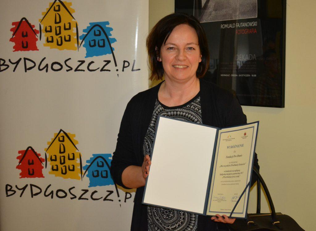 Zdjęcie kobiety trzymającej wyróżnienie dla Fundacji Pro Omnis