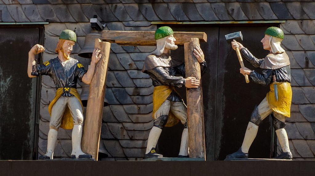Zdjęcie figur z drewna przedstawiających średniowiecznych budowniczych