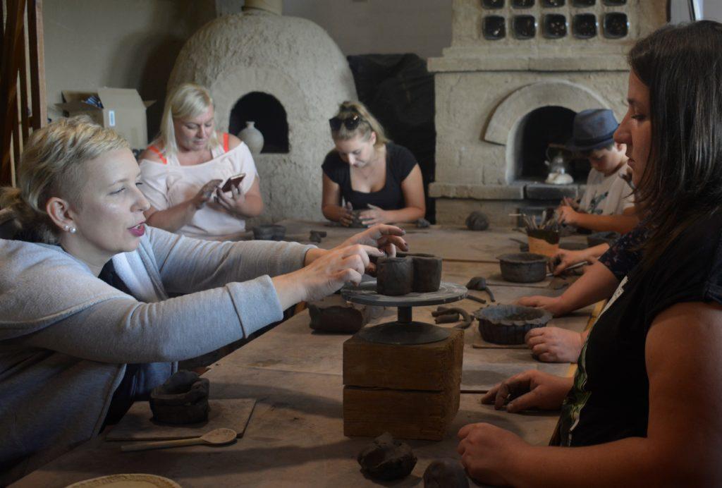 Zdjęcie uczestników warsztatów rzemieślniczych którzy lepią naczynia w glinie