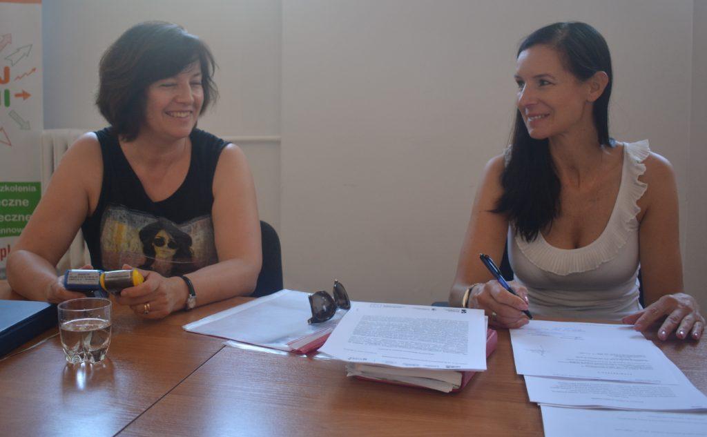 Zdjęcie dwóch kobiet siedzących przy stole z dokumentami - zdjęcie numer 2