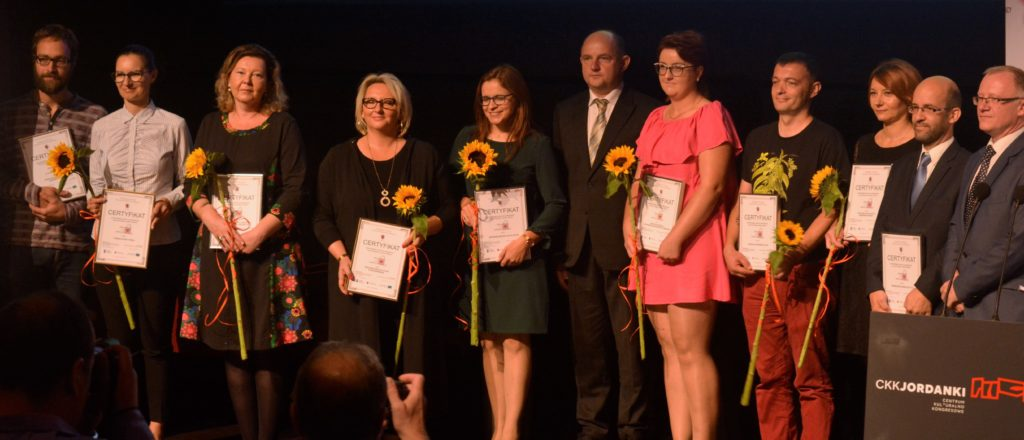 """Uczestnicy akcji """"więcej niż biznes"""" trzymający słoneczniki oraz certyfikaty - zdjęcie numer 1"""