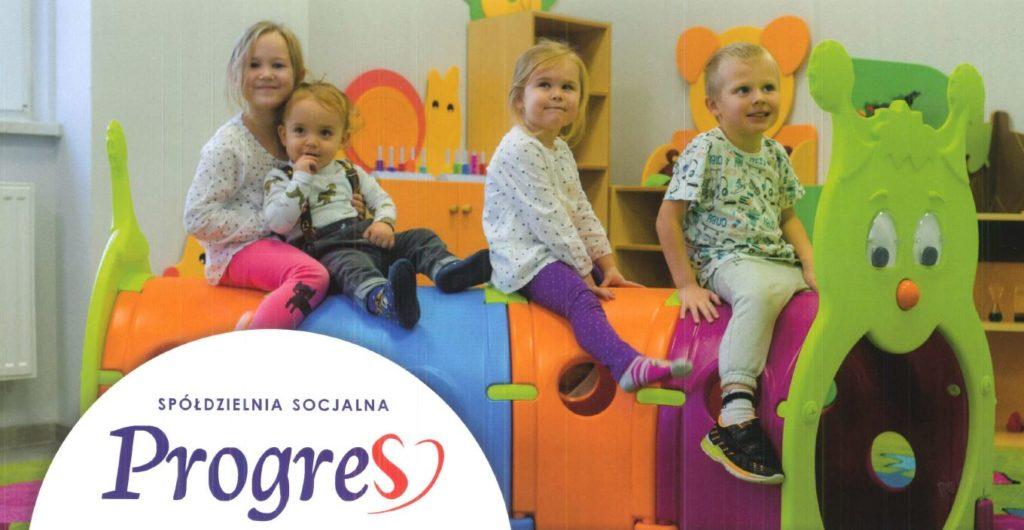 """Zdjęcie dzieci w pokoju zabaw z logiem spółdzielni socjalnej """"Progres"""""""