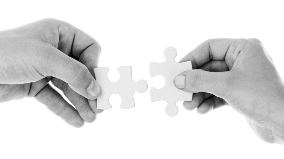 Czarnobiałe zdjęć rąk trzymających dwa białe puzle