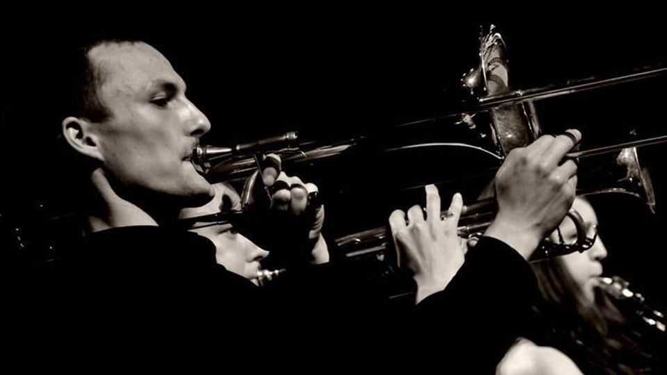 Czarnobiałe zdjęcie Krzysztofa Błaszczaka grającego na puzonie