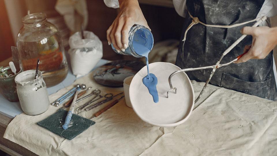 Zdjęcie przedstawia rzemieślnika który wylewa niebieską farbę na biały wklęsły okrąg przytrzymany narzędziem