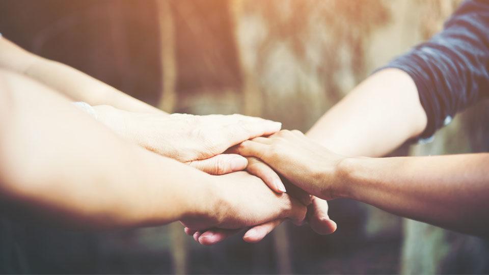 Zdjęcie przedstawia osoby zbliżające ręce w jedno miejsce