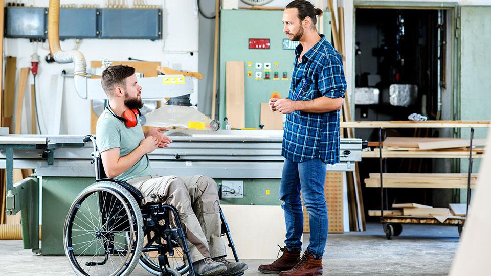 Obrazek przedstawia mężczyznę na wózku inwalidzkim, który rozmawia z mężczyzną stojącym obok niego