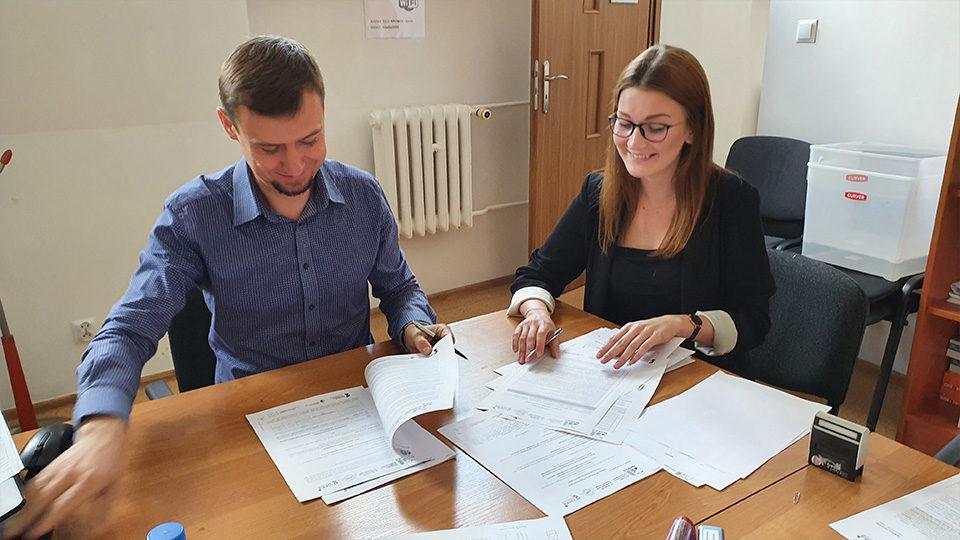 Zdjęcie przedstawia dwóch pracowników firmy Pro Social którzy czytają i wypełniają dokumenty
