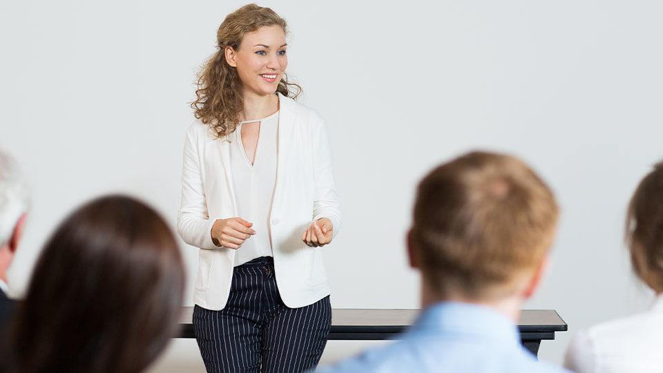 Zdjęcie przedstawia kobietę przeprowadzającą szkolenie z potencjalnymi pracownikami