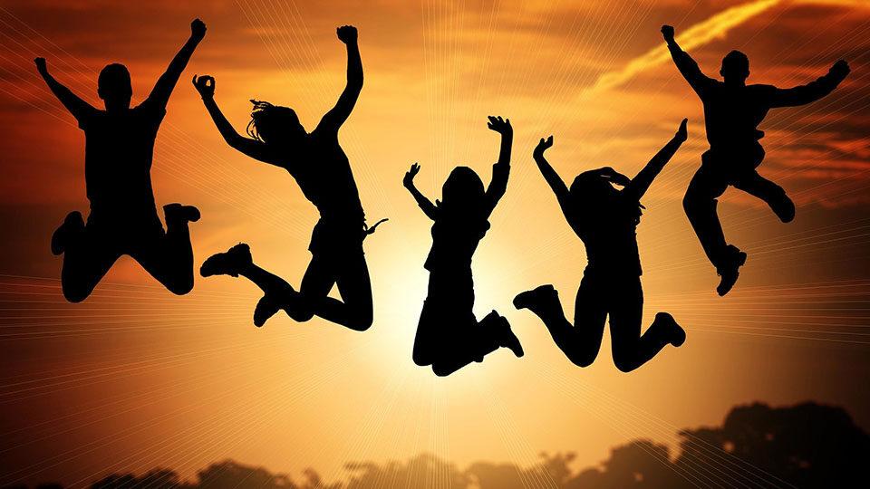 Grafika przedstawiająca grupę osób robiącą wyskok na tle słońca