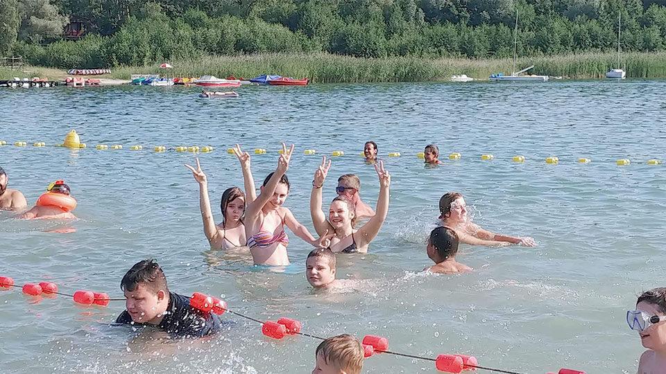 Zdjęcie na którym znajdują się młodzi ludzie na kąpielisku. Wszyscy są uśmiechnięci, bawią się, niektórzy z nich machają rękami, uśmiechając się do zdjęcia.