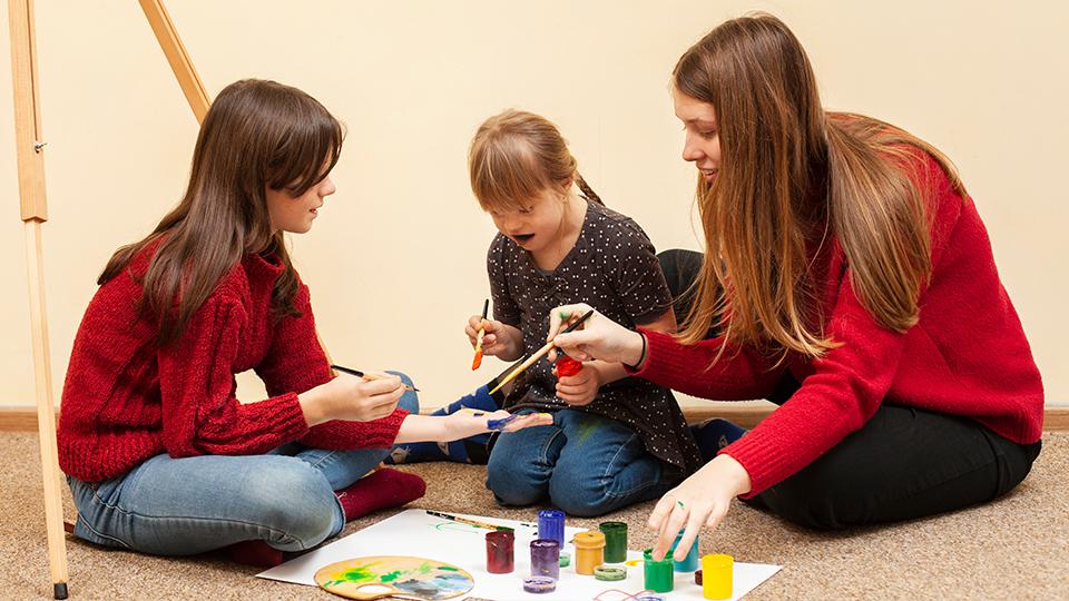 Zdjęcie na którym animatorki wraz z dziewczynką malują dłonie farbkami.