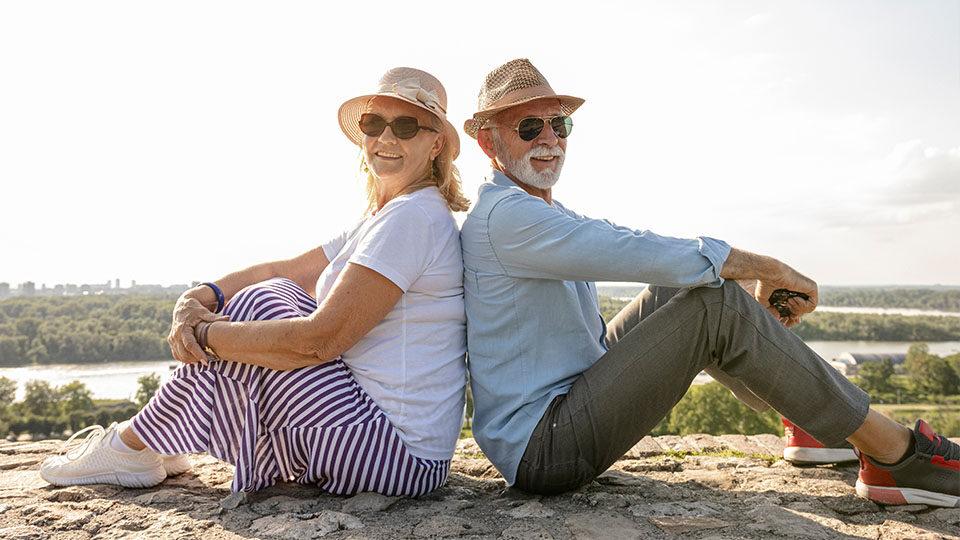 Para starszych ludzi siedzi do siebie plecami z widokiem na rzekę.