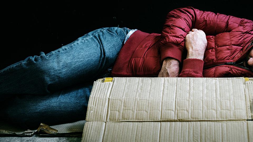 Zdjęcie przedstawia bezdomnego mężczyznę śpiącego na kartonach.