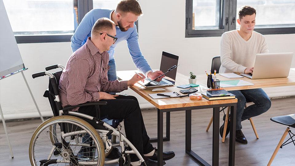 Osoba z niepełnosprawnością na wózku inwalidzkim w pracy.