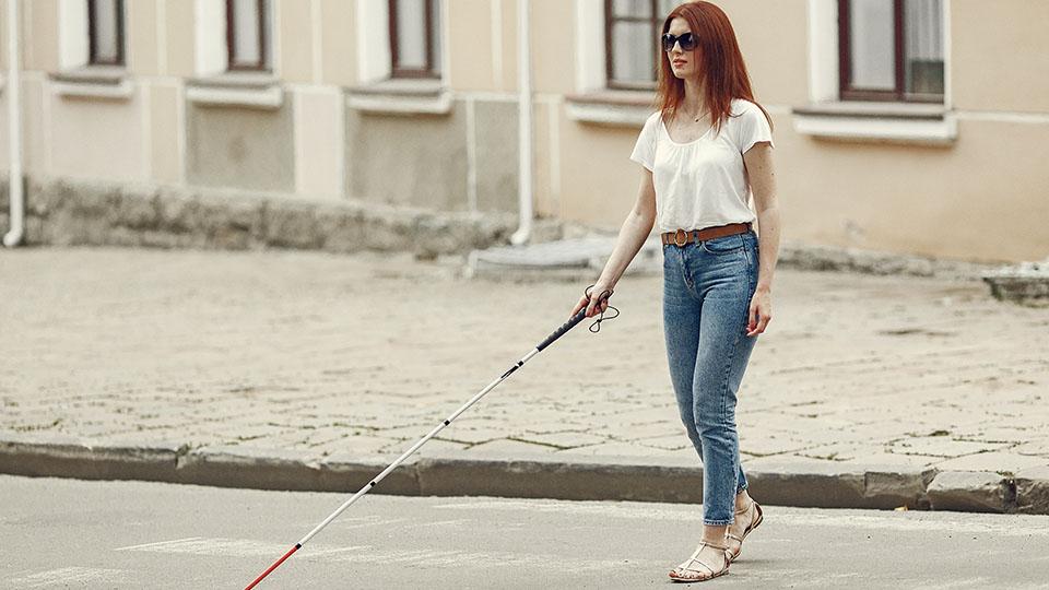 Niewidoma kobieta przechodząca na pasach przez jezdnię.