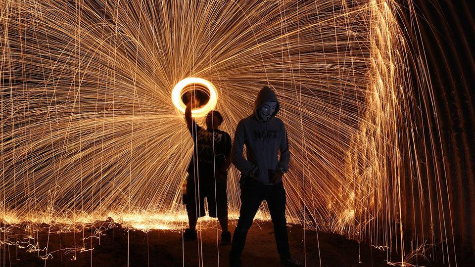 Zdjęcie przedstawia dwie postacie podczas pokazu ognia.