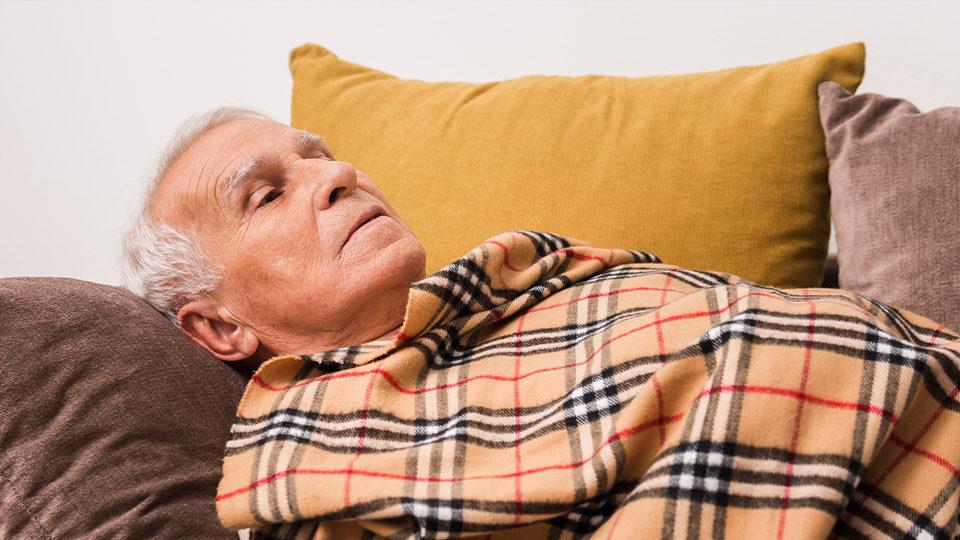 Starszy mężczyzna leżący pod kocem