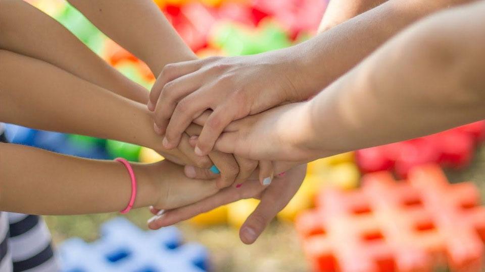 Obrazek przedstawia splątane dłonie ludzi.