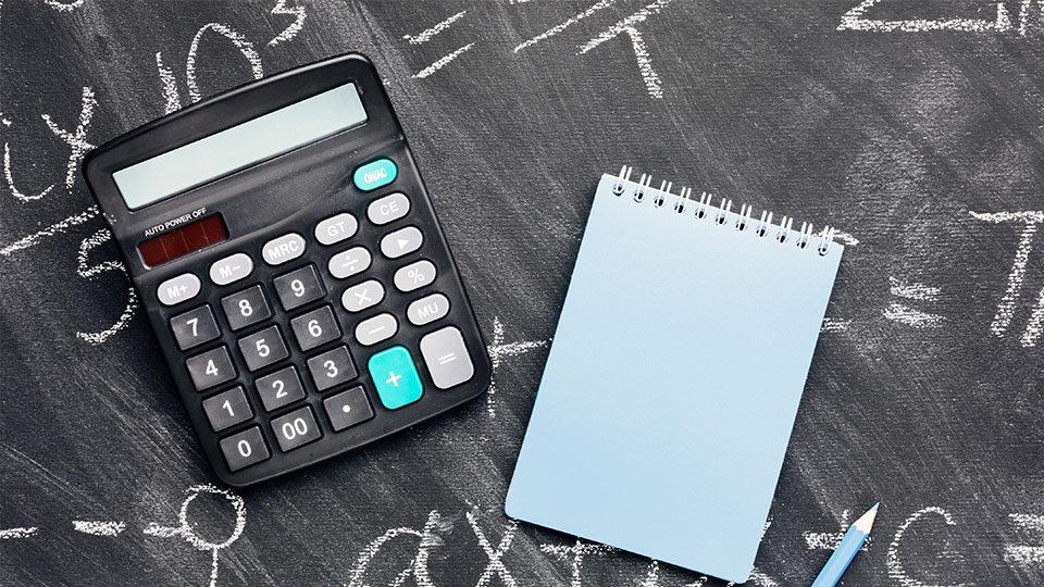 Na zdjęciu widoczny jest kalkulator i notes.