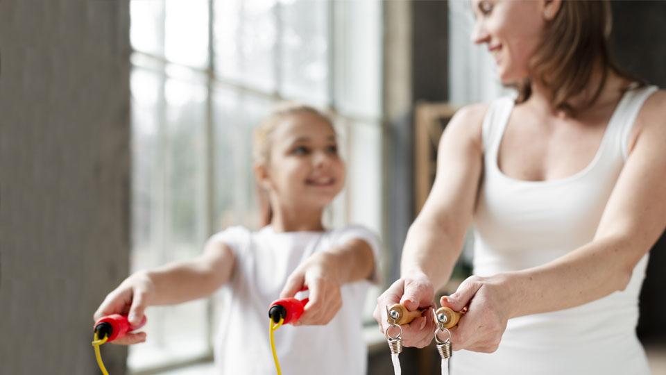 Grafika dotycząca programu Sport dla Wszystkich: Mama z córka podczas skakania na skakance.