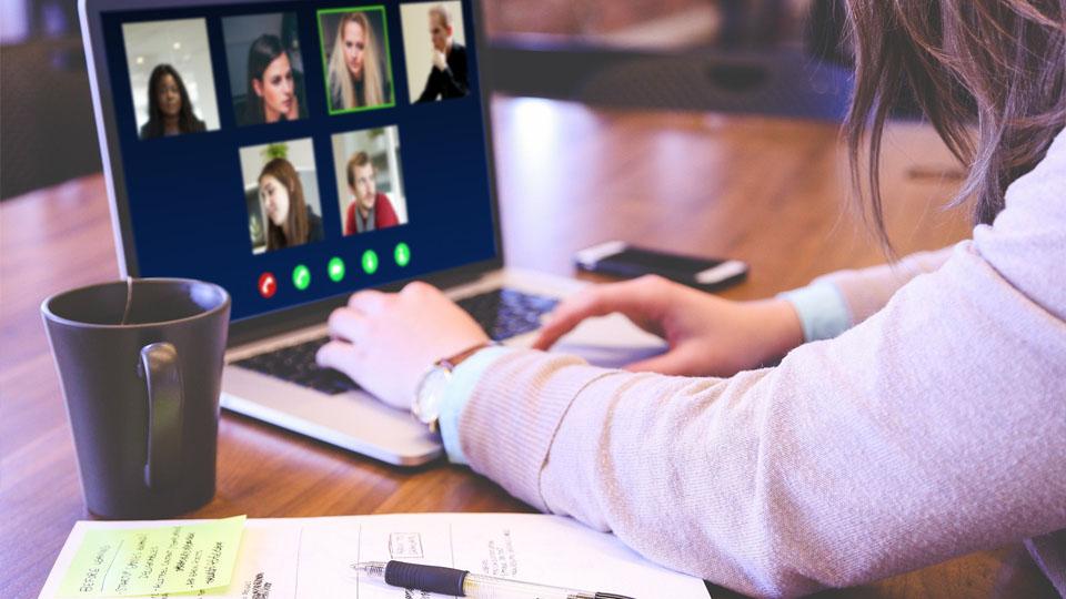 Obraz przedstawia osobę pracującą na laptopie