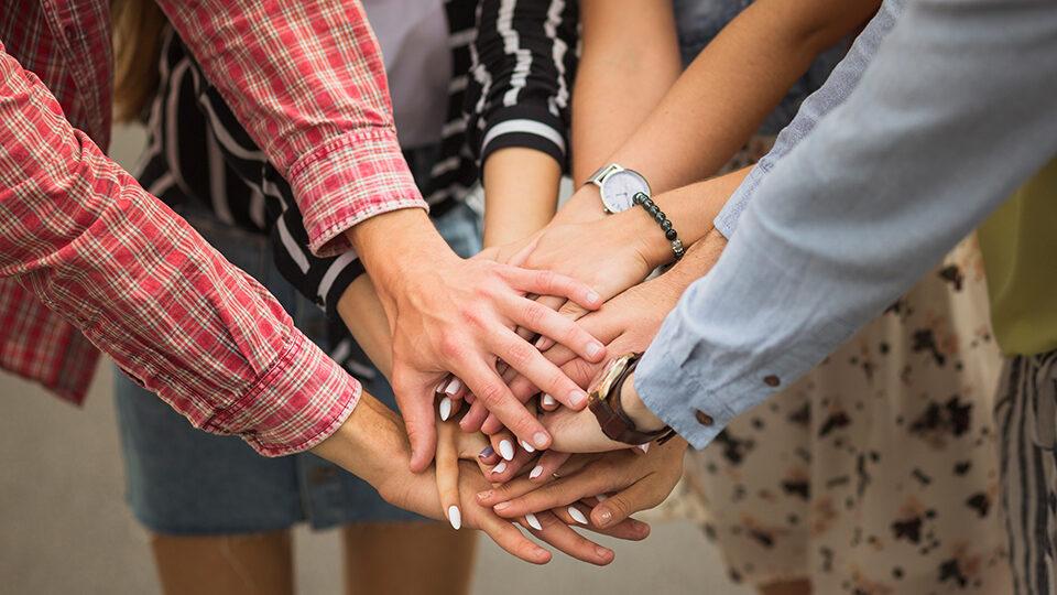 Na zdjęciu grupa ludzi z wyciągniętymi rękoma.