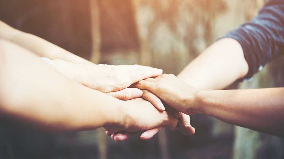 Na zdjęciu grupa ludzi okazująca wsparcie przez podanie sobie rąk.