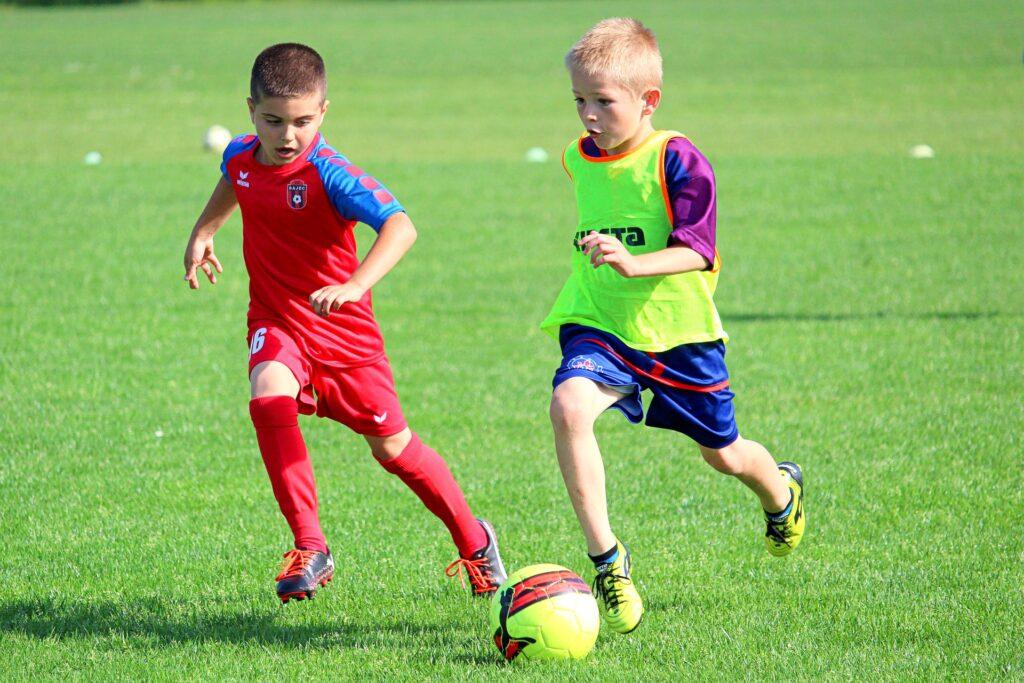 chłopcy na boisku grają w piłkę nożną