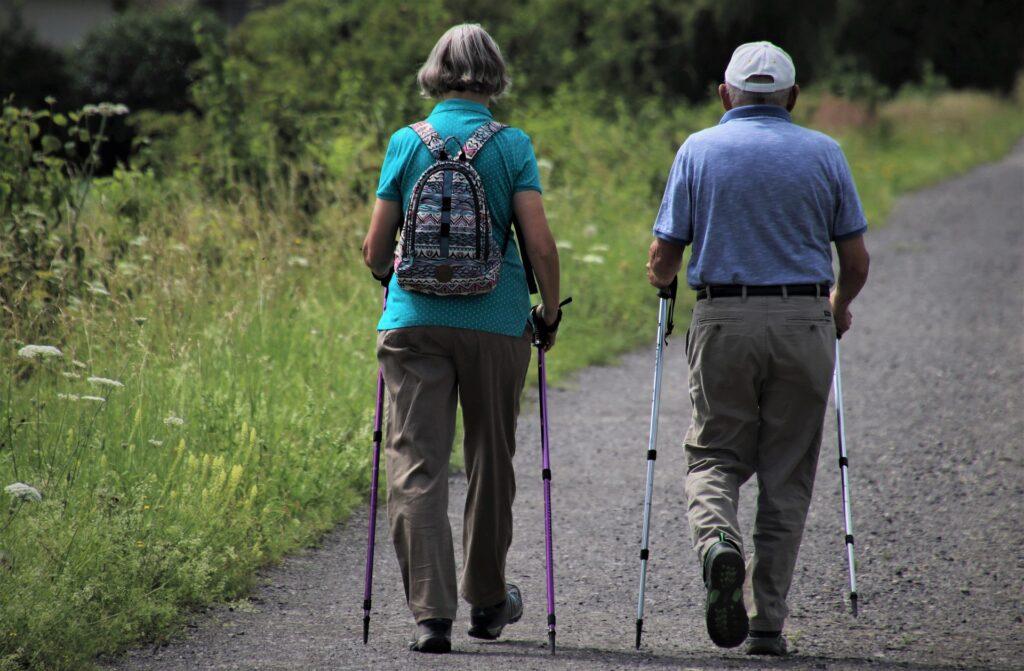 starszy mężczyzna i kobieta idą z kijkami nordic walking