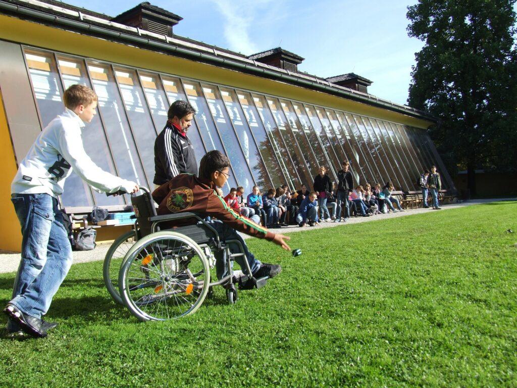 chłopiec na wózku inwalidzkim gra na boisku