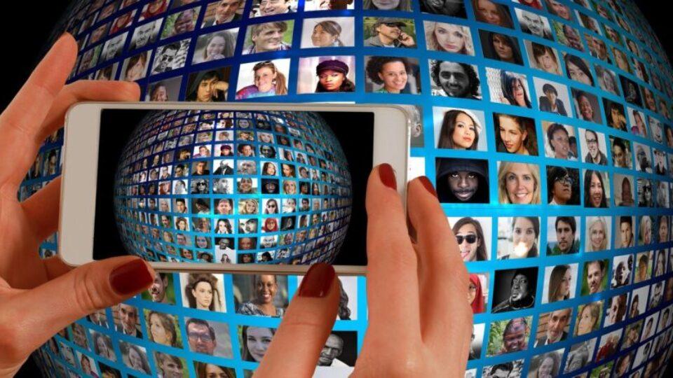 telefon komórkowy robiący zdjęcie kuli ziemskiej z twarzami ludzi
