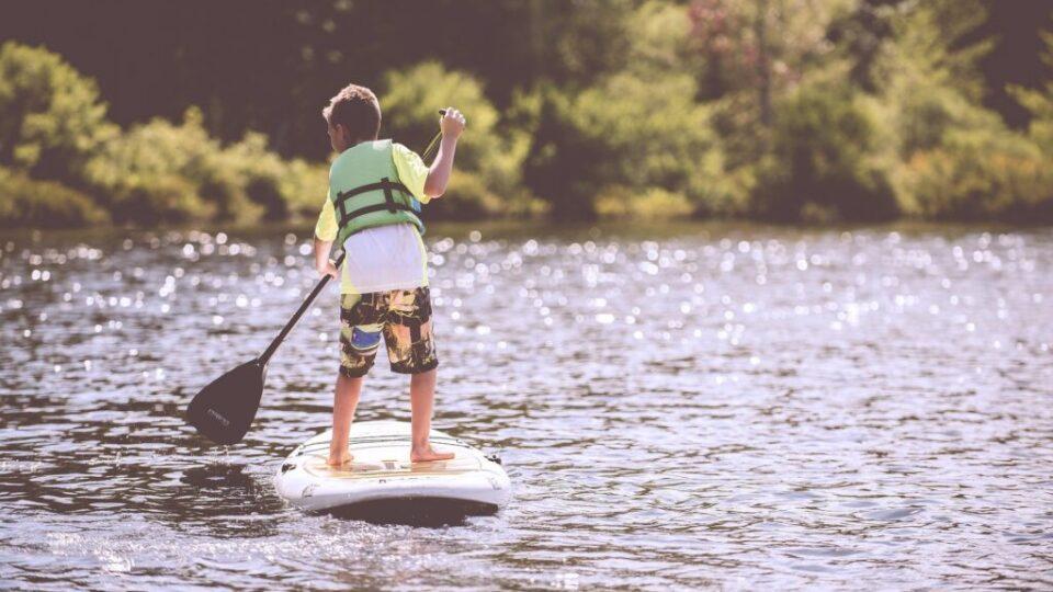 dziecko z wiosłem na desce na jeziorze