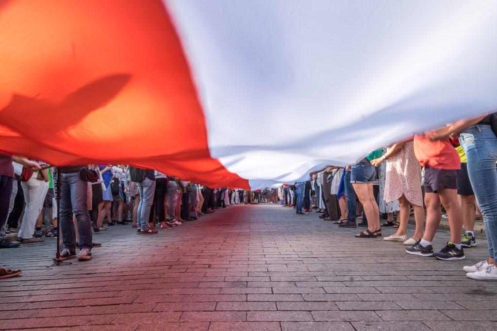 ludzie trzymający wielką flagę Polski