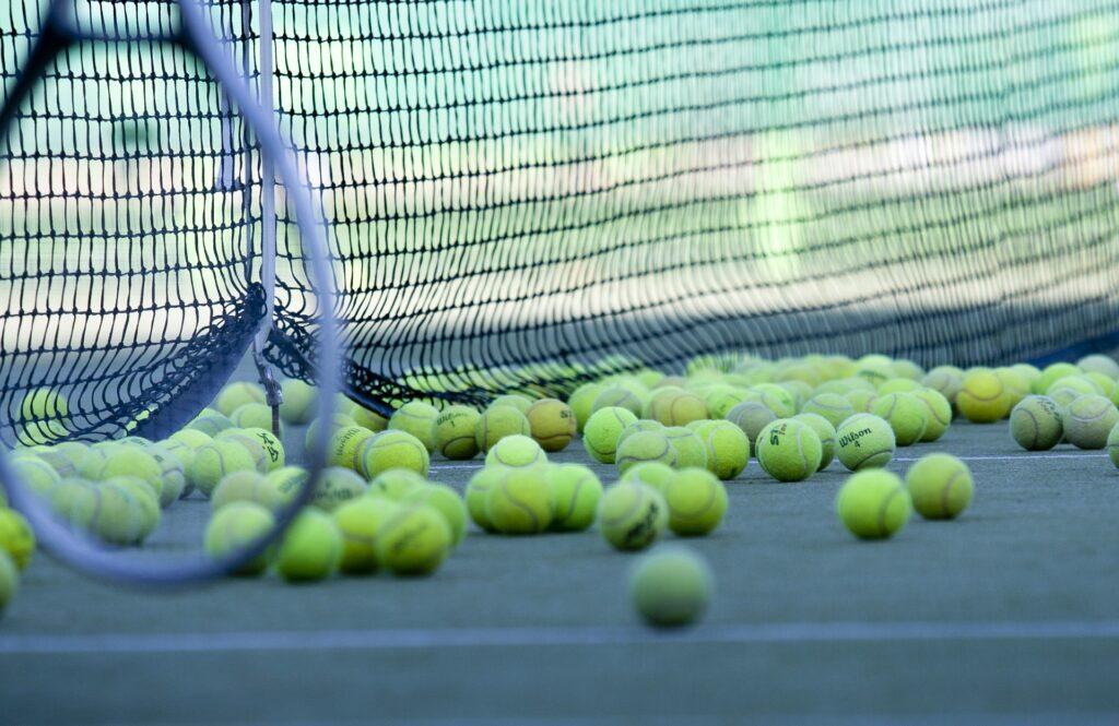 rakieta i piłeczki do tenisa przy siatce
