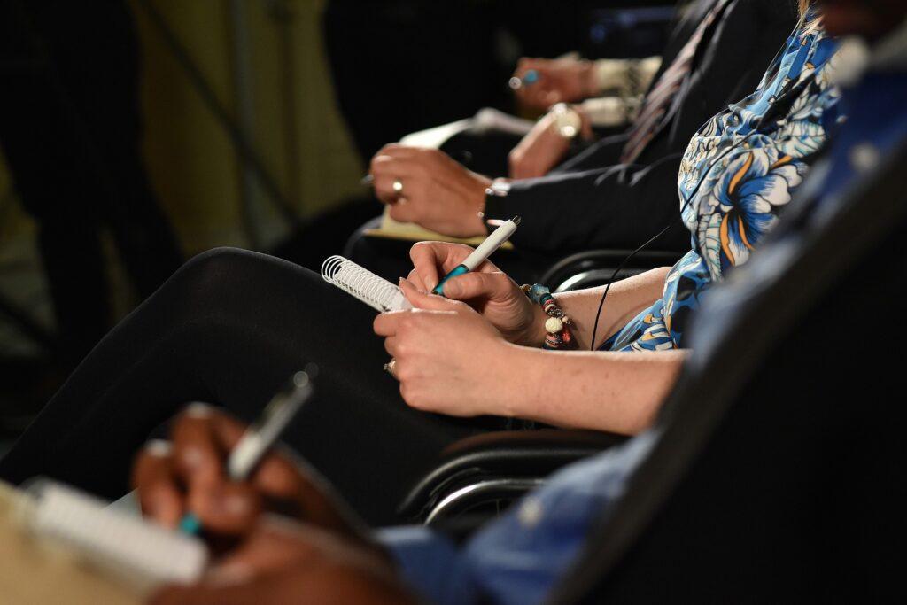 ręce ludzi robiących notatki