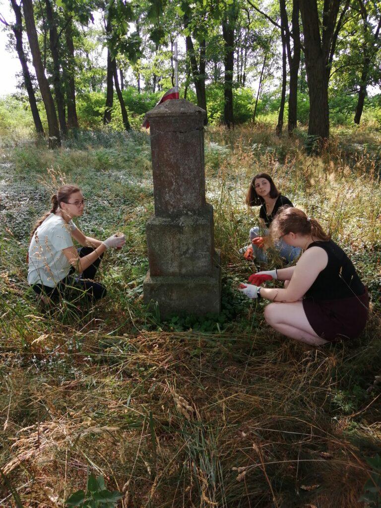 młode kobiety porządkują grób na Ukrainie